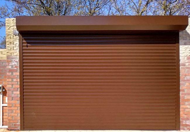 Автоматичні ролетні ворота з електропривідом коричневого кольору фото